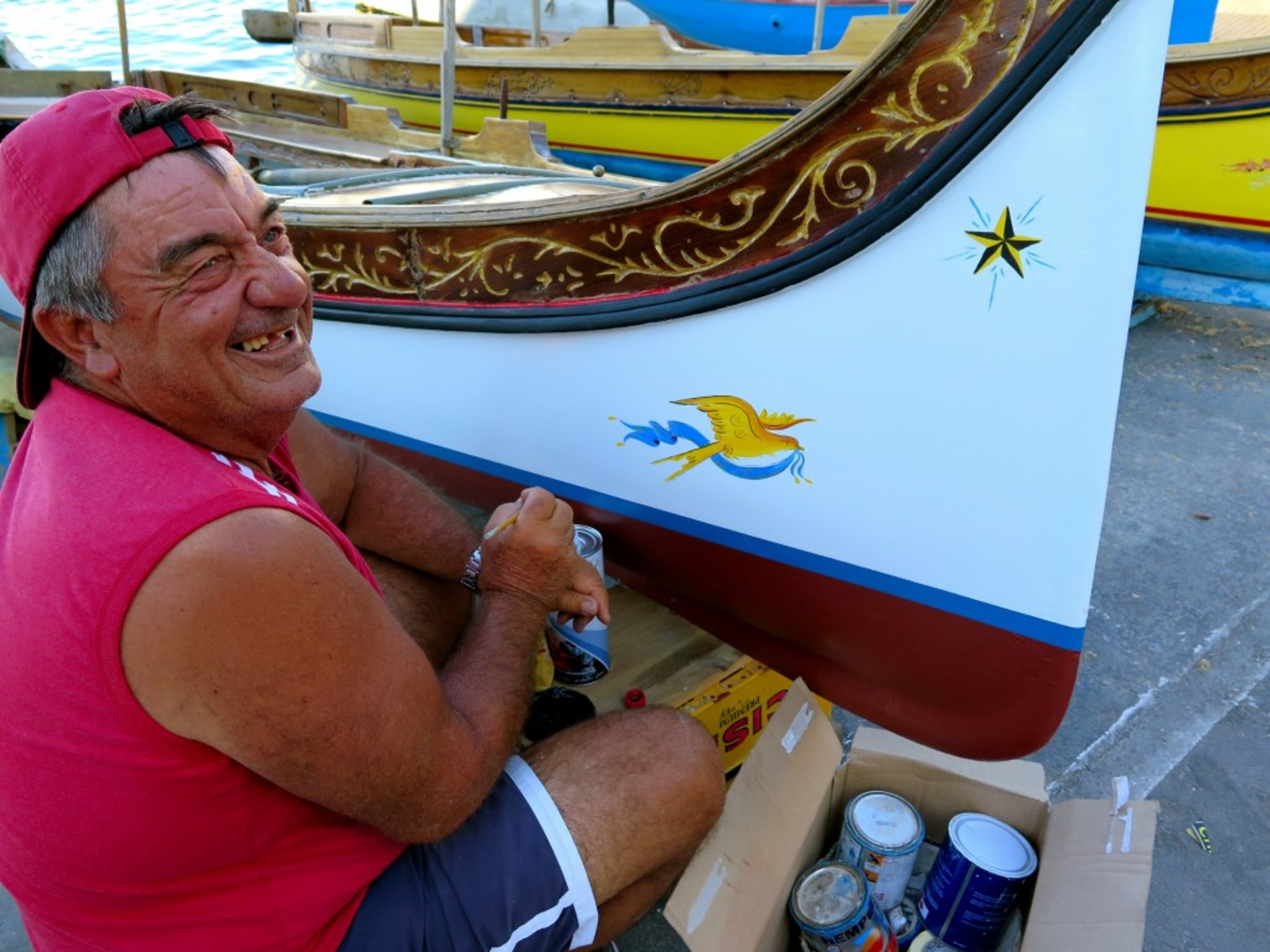 Local fisherman painting his boat...